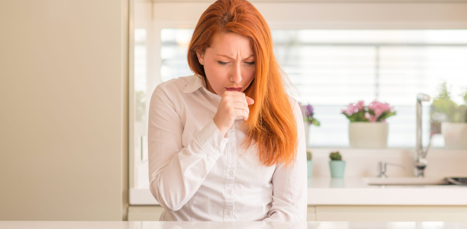 Redhead woman at kitchen feeling unwell and coughing as symptom for cold or bronchitis. Healthcare concept.